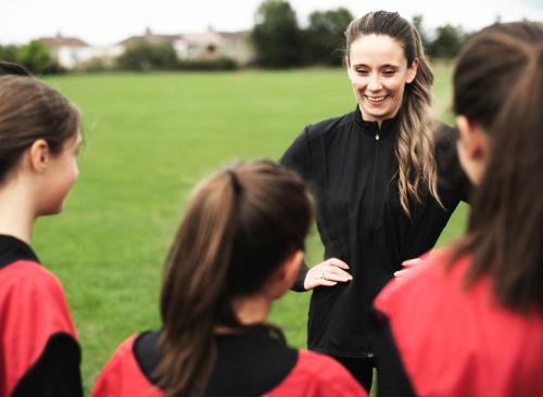 PE Teacher coaching children